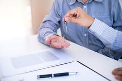 Διευθυντής πωλήσεων που δίνει το έγγραφο αίτησης υποψηφιότητας συμβουλών, που εξετάζει την προσφορά ενυπόθηκου δανείου για την ασ στοκ φωτογραφία με δικαίωμα ελεύθερης χρήσης
