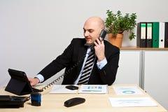 Διευθυντής στο τηλέφωνο ενώ συγκρίνει τα στοιχεία όσον αφορά την ταμπλέτα Στοκ Εικόνες