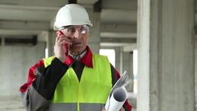 Διευθυντής των εργασιών με το κόκκινο smartphone στο εργοτάξιο οικοδομής απόθεμα βίντεο