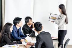 Διευθυντής Oung που στέκεται παρουσιάζοντας το οικονομικό διάγραμμα ενώ άλλοι που ακούνε την στοκ εικόνες