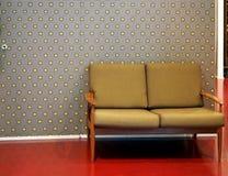 Διθέσιος αναδρομικός καναπές στο κόκκινο πάτωμα Στο υπόβαθρο, ταπετσαρία με το γκρίζο και κίτρινο άνευ ραφής σχέδιο Στοκ φωτογραφία με δικαίωμα ελεύθερης χρήσης
