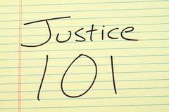 Δικαιοσύνη 101 σε ένα κίτρινο νομικό μαξιλάρι Στοκ Φωτογραφίες