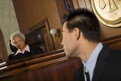 Δικαστής και μάρτυρας που εξετάζουν μεταξύ τους στοκ εικόνα με δικαίωμα ελεύθερης χρήσης