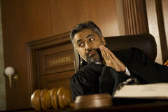 Δικαστής με τα χέρια Clasped που φαίνεται μακριά στο δικαστήριο δωμάτιο Στοκ Εικόνα
