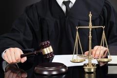Δικαστής με τη σφύρα και κλίμακα βάρους στο γραφείο Στοκ Εικόνες