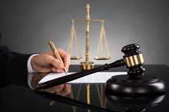 Δικαστής που γράφει σε χαρτί στο γραφείο Στοκ Φωτογραφίες