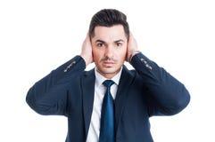 Δικηγόρος ή μεσίτης που καλύπτει τα αυτιά του με τους φοίνικες Στοκ Εικόνες