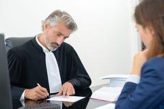 Δικηγόρος που υπογράφει το έγγραφο στην αρχή με το θηλυκό πελάτη στοκ φωτογραφία με δικαίωμα ελεύθερης χρήσης