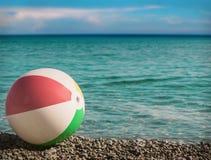 Διογκώσιμη σφαίρα παιχνιδιών στην παραλία ενάντια στη θάλασσα Στοκ φωτογραφία με δικαίωμα ελεύθερης χρήσης