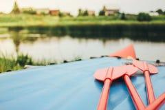 Διογκώσιμο καταμαράν για τον ποταμό που και που αλιεύει στην ακτή χλόης, εστίαση στα κουπιά στοκ εικόνες με δικαίωμα ελεύθερης χρήσης