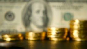 Διοικητική αποδοτικότητα Αυξανόμενοι σωροί των χρυσών νομισμάτων στο υπόβαθρο σημειώσεων δολαρίων Περιστροφή, στρίψιμο, στροβιλιμ απόθεμα βίντεο