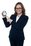Διοικητικός συνεργάτης που δείχνει προς το ρολόι Στοκ Εικόνες