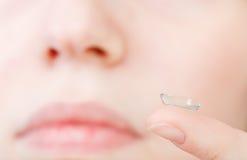 Διορθωτικός φακός στο δάχτυλο κοντά στο θηλυκό πρόσωπο στοκ εικόνα