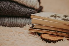 Διπλωμένα πλεκτά μάλλινα πουλόβερ, σωρός των παλαιών βιβλίων σε ένα άνετο χνουδωτό μπεζ κάλυμμα στοκ φωτογραφίες