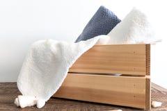 Διπλωμένες διαφορετικές πετσέτες λουτρών στο ξύλινο κιβώτιο στον καφετή ξύλινο πίνακα SPA και wellness, κλωστοϋφαντουργικό προϊόν Στοκ φωτογραφία με δικαίωμα ελεύθερης χρήσης