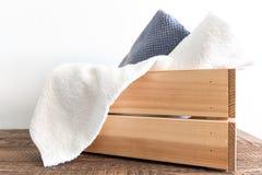 Διπλωμένες διαφορετικές πετσέτες λουτρών στο ξύλινο κιβώτιο στον καφετή ξύλινο πίνακα SPA και wellness, κλωστοϋφαντουργικό προϊόν Στοκ Φωτογραφίες