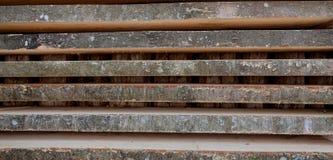 Διπλωμένες ξύλινες καφετιές και γκρίζες σανίδες σε ένα πριονιστήριο Συσσωρευμένοι πίνακες κληθρών ως σύσταση στοκ εικόνες με δικαίωμα ελεύθερης χρήσης
