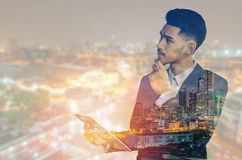 Διπλός νέος ασιατικός επιχειρηματίας έκθεσης με την επικοινωνία ταμπλετών που απομονώνεται στο υπόβαθρο πόλεων στοκ εικόνα με δικαίωμα ελεύθερης χρήσης