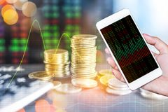 Διπλό χέρι έκθεσης που κρατά το έξυπνους τηλέφωνο και το σωρό των νομισμάτων πέρα από την οθόνη χρηματιστηρίου Στοκ Φωτογραφίες