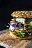 Διπλό burger καταστρωμάτων με το τυρί και τα φυλλώδη πράσινα Στοκ Φωτογραφίες