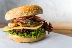Διπλό burger καταστρωμάτων στο ξύλινο επιτραπέζιο γκρίζο υπόβαθρο στοκ εικόνα