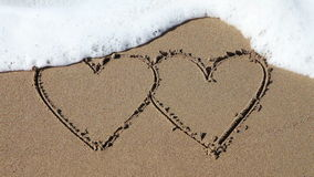 Διπλές καρδιές που σύρονται στην άμμο απόθεμα βίντεο