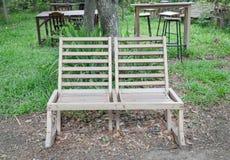 Διπλές υπαίθριες ξύλινες καρέκλες στον κήπο Στοκ Φωτογραφία