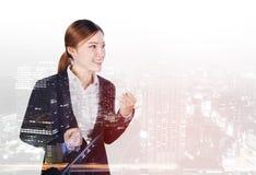 Διπλή έκθεση της επιτυχούς επιχειρησιακής γυναίκας με αυξημένο το βραχίονας πνεύμα στοκ εικόνες