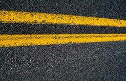 Διπλή κίτρινη γραμμή σε έναν δρόμο ασφάλτου Στοκ Φωτογραφία