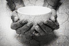 Διπλή πείνα έκθεσης που ικετεύει τα χέρια και το ξηρό χώμα Στοκ φωτογραφία με δικαίωμα ελεύθερης χρήσης