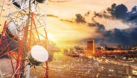 Διπλοί πύργοι τηλεπικοινωνιών έκθεσης με τις κεραίες TV και δορυφορικό πιάτο στο ηλιοβασίλεμα, με το υπόβαθρο πόλεων Στοκ Εικόνες