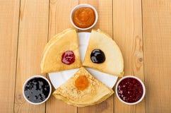 Διπλωμένες ρωσικές τηγανίτες στο πιάτο και κύπελλα με τη διαφορετική μαρμελάδα Στοκ Φωτογραφίες