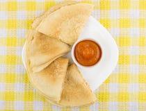Διπλωμένες ρωσικές τηγανίτες στο πιάτο και κύπελλα με τη μαρμελάδα ροδάκινων Στοκ Εικόνες