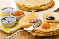 Διπλωμένες ρωσικές τηγανίτες στο πιάτο με τη διαφορετικά μαρμελάδα και το δίκρανο Στοκ φωτογραφία με δικαίωμα ελεύθερης χρήσης