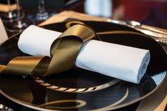 Διπλωμένη πετσέτα που τοποθετούνται στο πιάτο στον πίνακα στο εστιατόριο Στοκ Εικόνα