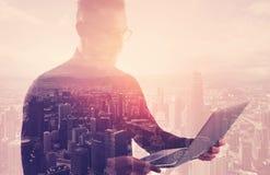 Διπλός επιχειρηματίας έκθεσης που φορά το μαύρα πουκάμισο και τα γυαλιά Τραπεζίτης που κρατά τα σύγχρονα χέρια σημειωματάριων Χρη Στοκ εικόνα με δικαίωμα ελεύθερης χρήσης