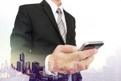 Διπλός επιχειρηματίας έκθεσης που χρησιμοποιεί το smartphone με το υπόβαθρο άποψης πόλεων Στοκ εικόνα με δικαίωμα ελεύθερης χρήσης