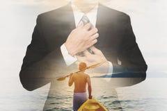 Διπλός επιχειρηματίας έκθεσης στο κοστούμι με έναν τύπο που τραβά το καγιάκ στον ωκεανό στο θερινό ηλιοβασίλεμα Στοκ εικόνες με δικαίωμα ελεύθερης χρήσης