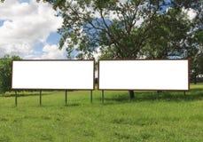 Διπλός κενός πίνακας διαφημίσεων μπροστά από τον όμορφο νεφελώδη ουρανό Στοκ Εικόνα