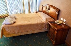 Διπλό κρεβάτι στο δωμάτιο ξενοδοχείου με το εκλεκτής ποιότητας σχέδιο Στοκ Εικόνες