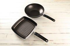 Διπλό μαύρο τηγάνι πέρα από το άσπρο ξύλο Στοκ φωτογραφίες με δικαίωμα ελεύθερης χρήσης