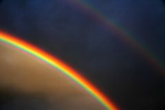 Διπλό ουράνιο τόξο μετά από τη θύελλα και το μαύρο ουρανό Στοκ Φωτογραφία
