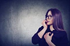 Διστακτική ανήσυχη γυναίκα που δαγκώνει τα νύχια της που φαίνονται sideway στοκ φωτογραφίες με δικαίωμα ελεύθερης χρήσης
