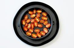 Διχοτομημένες ντομάτες κερασιών σε ένα μαύρο πιάτο σε ένα άσπρο υπόβαθρο, άνωθεν στοκ φωτογραφία με δικαίωμα ελεύθερης χρήσης
