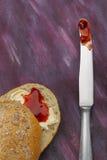 Διχοτομημένος wholemeal ρόλος με τη βουτύρου και κόκκινη μαρμελάδα και μαχαίρι με τη μαρμελάδα στοκ φωτογραφίες με δικαίωμα ελεύθερης χρήσης