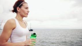 Διψασμένη γυναίκα ικανότητας που στηρίζεται παίρνοντας ένα σπάσιμο με την κατανάλωση μπουκαλιών νερό μετά από να εκπαιδεύσει Όμορ απόθεμα βίντεο