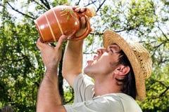 Διψασμένος νεαρός άνδρας με το πόσιμο νερό καπέλων αχύρου από ένα κεραμικό j Στοκ φωτογραφία με δικαίωμα ελεύθερης χρήσης