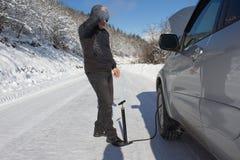 Διόγκωση της ρόδας ενός αυτοκινήτου Το άτομο επισκευάζει το ποδήλατο στο δάσος, χειμώνας Στοκ Εικόνες