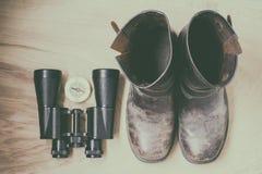 Διόπτρες, παλαιές μπότες και πυξίδα, ταξιδιωτικά ` s πράγματα, στο ξύλινο υπόβαθρο Στοκ φωτογραφία με δικαίωμα ελεύθερης χρήσης