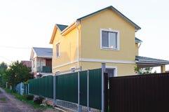 Διώροφο ιδιωτικό σπίτι πίσω από έναν φράκτη σιδήρου στοκ φωτογραφία με δικαίωμα ελεύθερης χρήσης